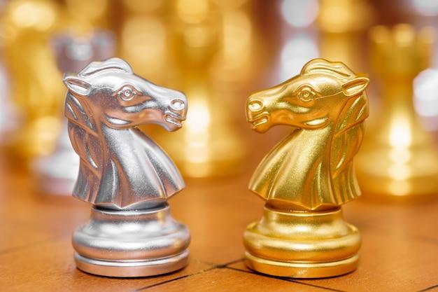 Goud en zilver paard van het schaakspel in het spel op schaakbord
