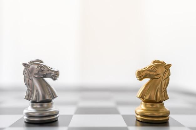 Goud en zilver ridder schaakstuk aangezicht tot aangezicht op schaakbord.