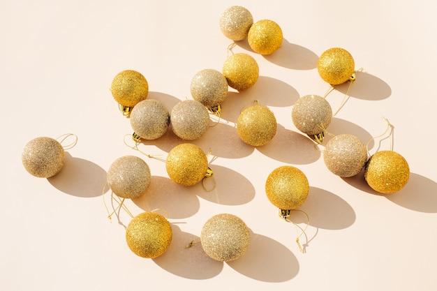 Goud glitter kerstballen decoratie op beige achtergrond. plat lag, bovenaanzicht.