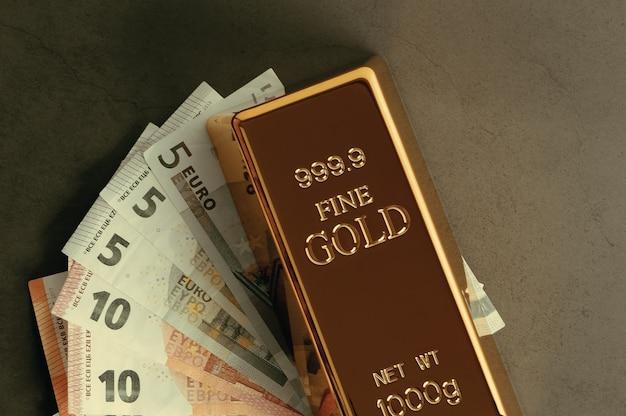 Goud metaal ingots in blokken op de achtergrond van eurobankbiljetten.