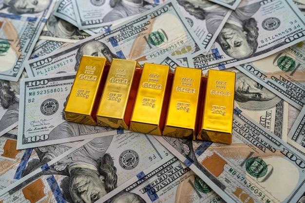 Goud op stapel amerikaanse dollarbiljetten als achtergrond. financiën en besparingsconcept