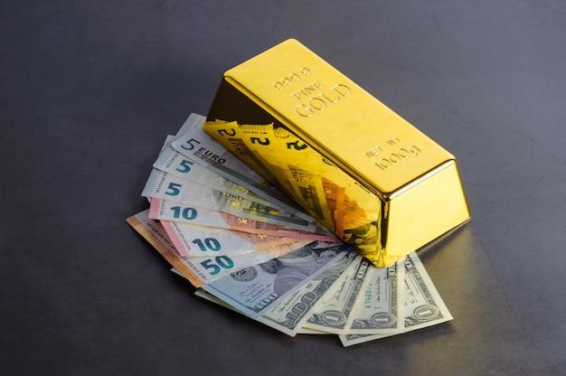 Goud staaf baar bullion tegen de achtergrond van de dollar en de euro rekeningen.