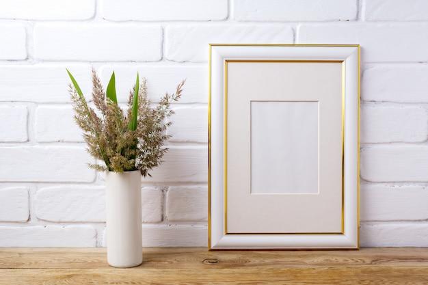 Goud versierd frame met gras en groene bladeren in cilindervaas