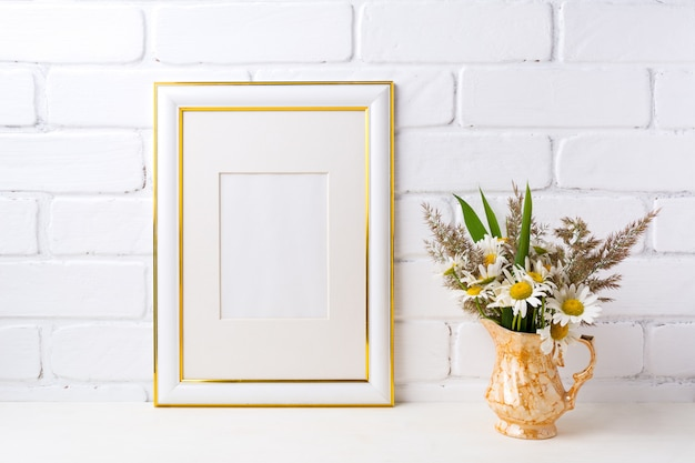 Goud versierd frame met kamille en gras in gouden vaas