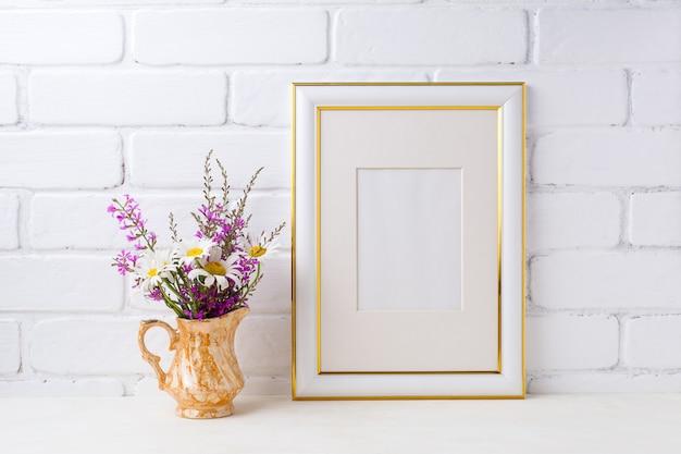 Goud versierd frame met kamille en paarse bloemen in gouden kruik