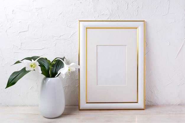 Goud versierd frame mockup met tedere witte lelie in vaas