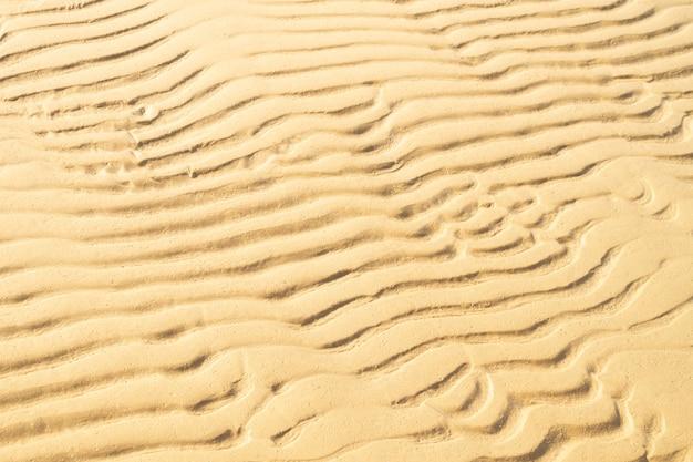 Goud zand met abstract golfpatroon. achtergrond van texure kust. zomer en vacotion concept