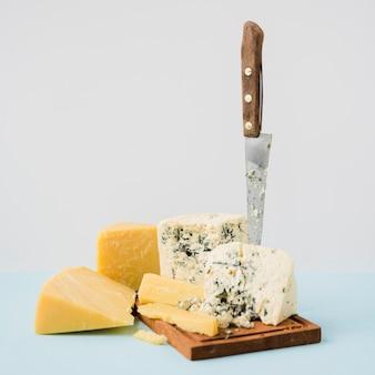 Gouda en blauwe kaas met scherp mes tegen witte achtergrond