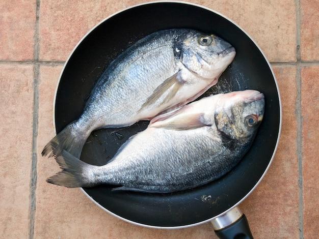Goudbrasem vissen op de pan klaar om te koken