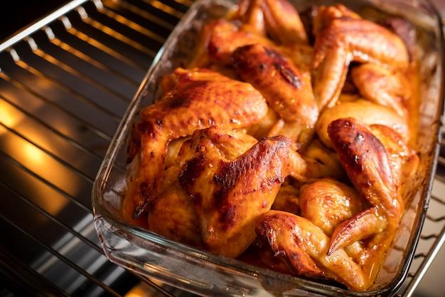 Goudbruine kippenvleugels liggen nog in de oven. licht van de ovenlamp