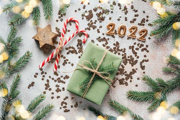 Gouden 2022 kaarsnummers met dennentakken, kerstversieringen en kerstverlichting met kerstverlichting bokeh