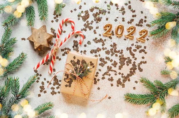 Gouden 2022 kaarsnummers met dennentakken, kerstversieringen en kerstverlichting