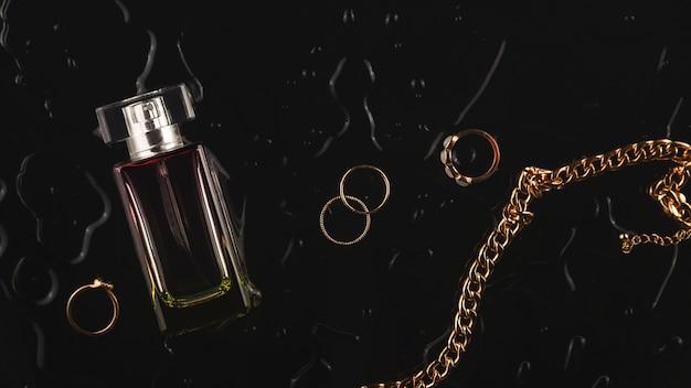 Gouden accessoires voor vrouwen en parfum op een zwarte achtergrond onder waterdruppels bovenaanzicht plat lag lay-out