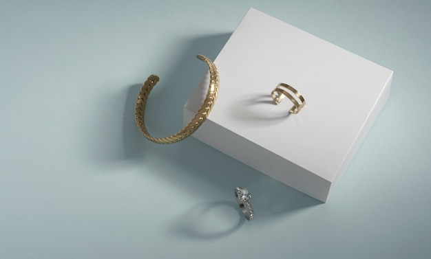 Gouden armband en ringen op witte doos op blauwe achtergrond met kopie ruimte