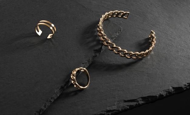 Gouden armband in kettingvorm en ringen op zwarte stenen platen