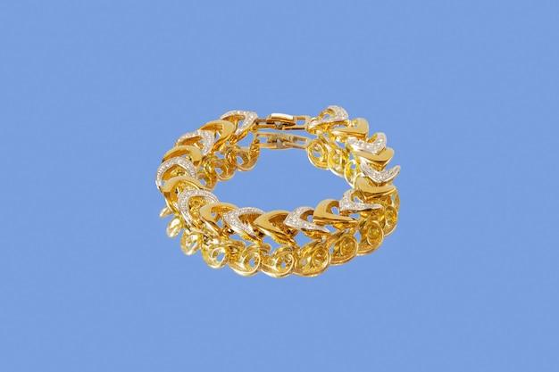 Gouden armband met wit platina en kleine diamanten op spiegelend oppervlak op blauw oppervlak.