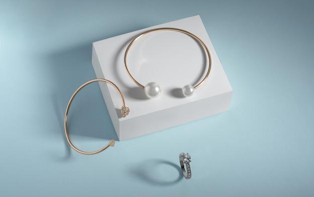 Gouden armbanden en ring met edelstenen op witte doos op blauwe achtergrond met kopie ruimte