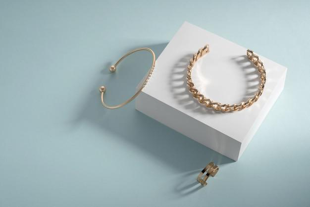 Gouden armbanden en ring op witte doos op blauwe achtergrond met kopie ruimte