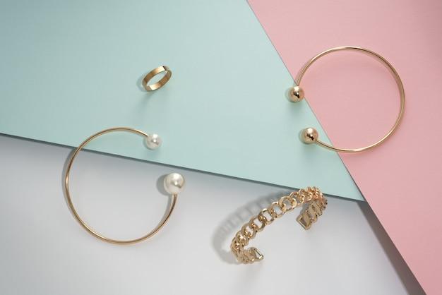 Gouden armbanden set en ring op pastel kleuren papier achtergrond