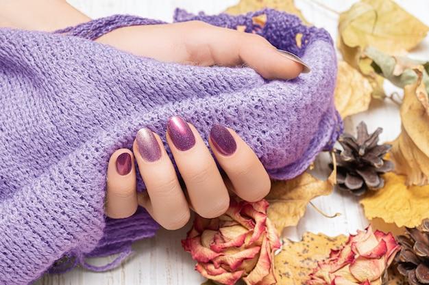 Gouden autunm-nageldesign. vrouw handen houden paarse wollen sjaal.