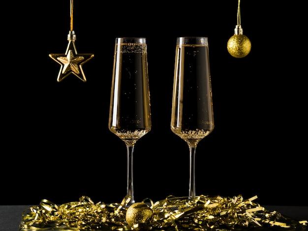 Gouden bal en ster en twee glazen mousserende wijn op een zwarte