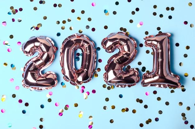 Gouden ballonnen in de vorm van nummers 2021 met kleurrijke confetti
