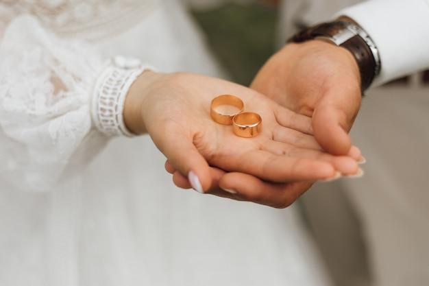 Gouden banden in de handen van bruid en bruidegom