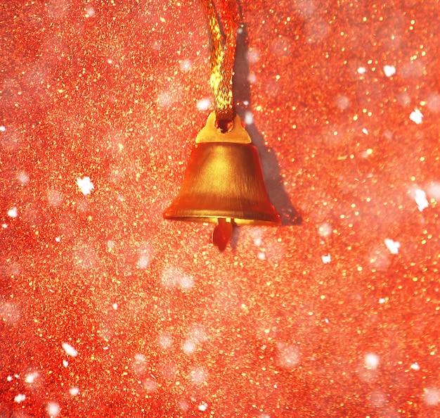 Gouden bel op glitter decoratieve achtergrond met sneeuweffect.