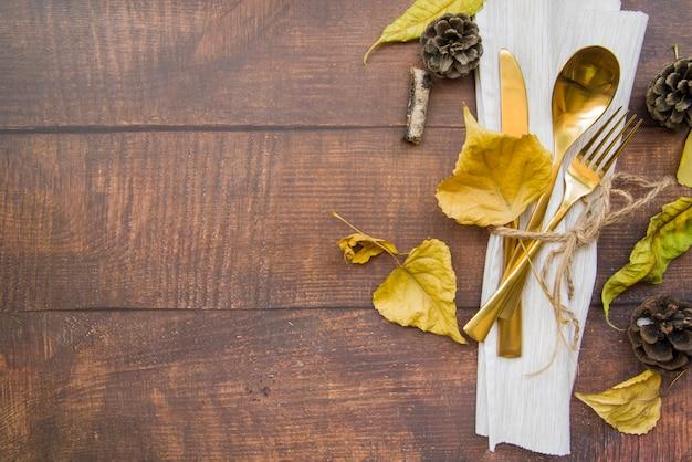Gouden bestek dat op wit servet wordt geplaatst