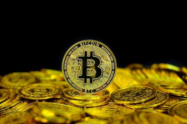 Gouden bitcoin cryptocurrency op stapel gouden munt op zwarte achtergrond
