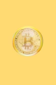 Gouden bitcoin drijvend in zeepbel op een gele achtergrond. cryptogeld, geld