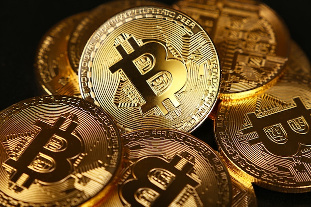 Gouden bitcoin fysieke munten geïsoleerd op zwarte achtergrond