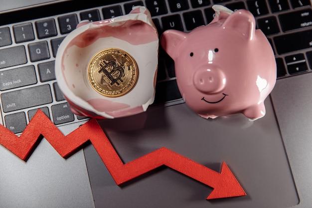 Gouden bitcoin gebroken spaarvarken en pijl naar beneden op laptop de daling van de waarde van bitcoin