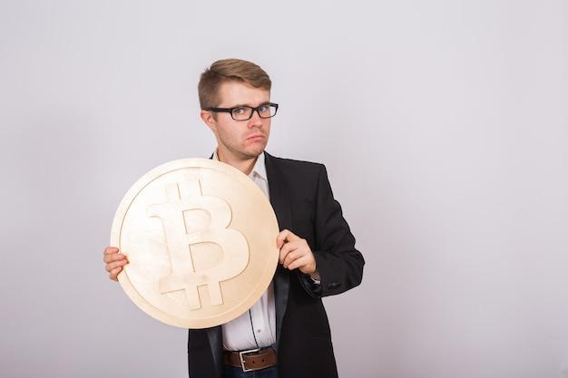 Gouden bitcoin in de hand van een man, digitaal symbool van een virtuele cryptocurrency.