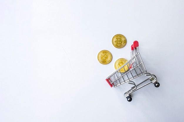 Gouden bitcoin in winkelwagen op witte tabelachtergrond. bovenaanzicht