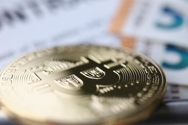 Gouden bitcoin ligt op tafel. geld verdienen met bitcoins zonder investeringen