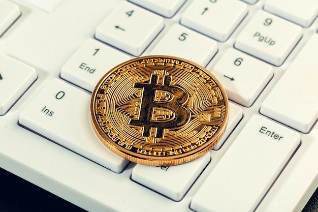 Gouden bitcoin munt cryptocurrency op het toetsenbord van de laptop.