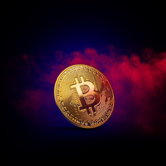 Gouden bitcoin munt is in rode en blauwe rook achtergrond. cryptocurrency-concept