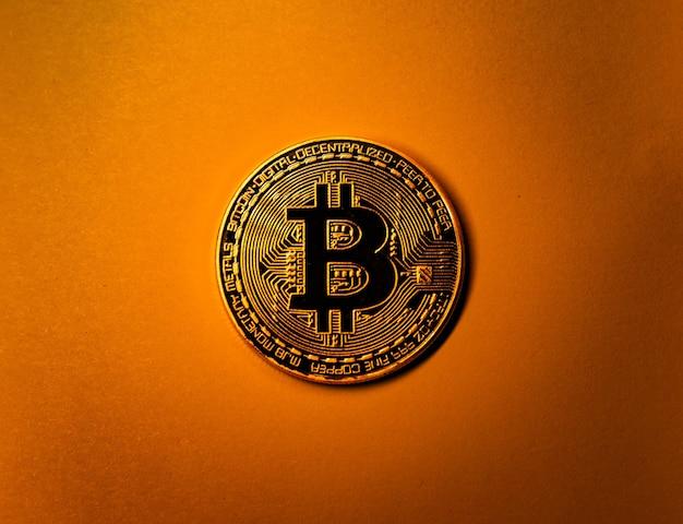 Gouden bitcoin munt op gele monochrome achtergrond