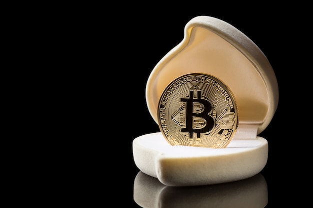 Gouden bitcoin-muntstuk in trouwringdoos die op zwarte achtergrond met bezinning wordt geïsoleerd