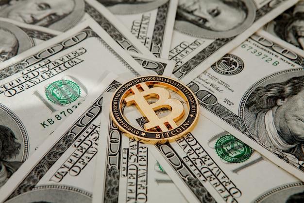 Gouden bitcoin op amerikaanse dollarbiljetten. elektronisch geldwisselingsconcept