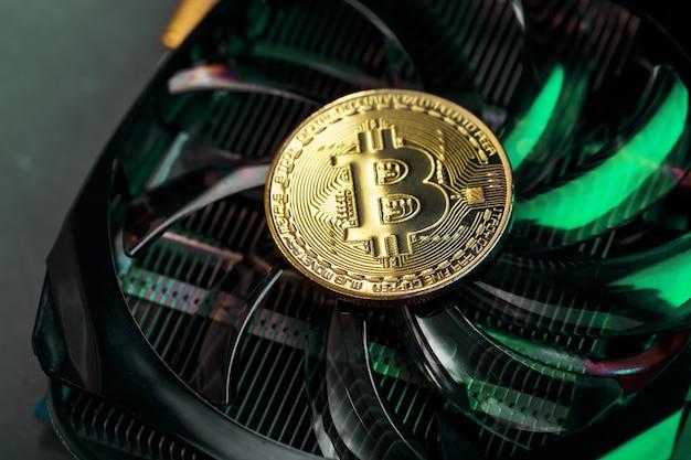 Gouden bitcoin op de videokaartkoeler met groene neonverlichting