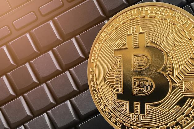Gouden bitcoin op de zwarte achtergrond van de toetsenbordcomputer.
