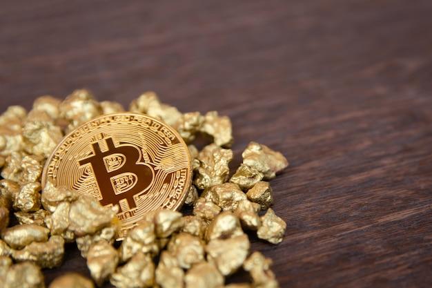 Gouden bitcoin op heuvel van goudklompje op donker hout
