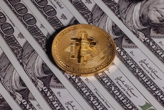 Gouden bitcoin op honderd-dollarbiljetten