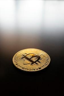 Gouden bitcoin op tafel met soft focus en achtergrondverlichting. cryptocurrency-concept