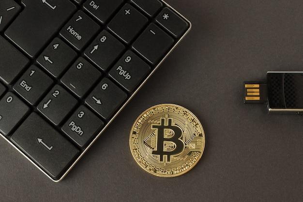 Gouden bitcoin, toetsenbord en flitsaandrijving op een donkere achtergrond hoogste mening