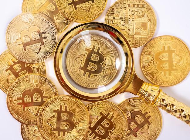 Gouden bitcoin vergrootglas op een onscherpe achtergrond van munten