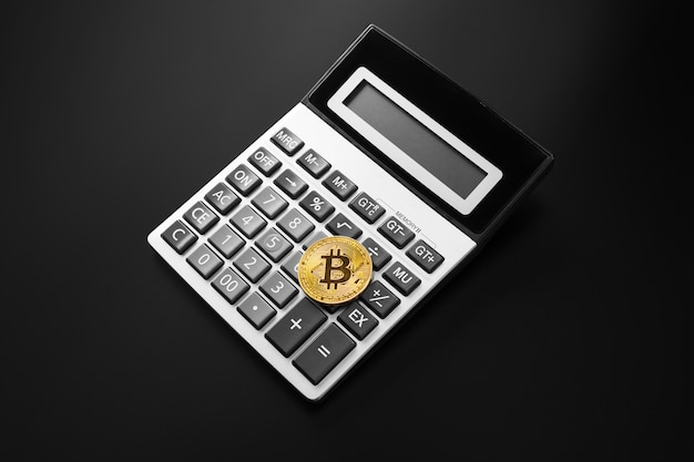 Gouden bitcoinmuntstuk op calculator dichte omhooggaand geïsoleerd op zwarte