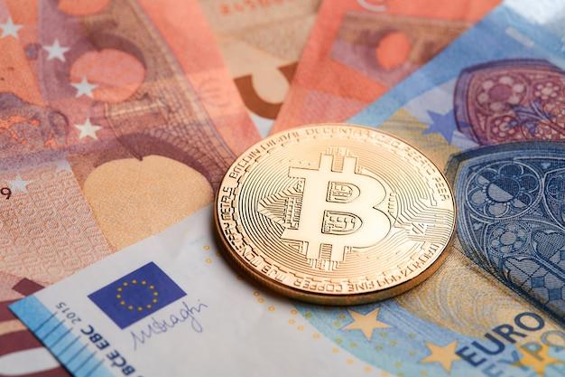 Gouden bitcoins die op euro bankbiljettenachtergrond worden gestapeld.